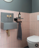 Bathroom with pink Mandarin stone tiles and grey sink, gold taps