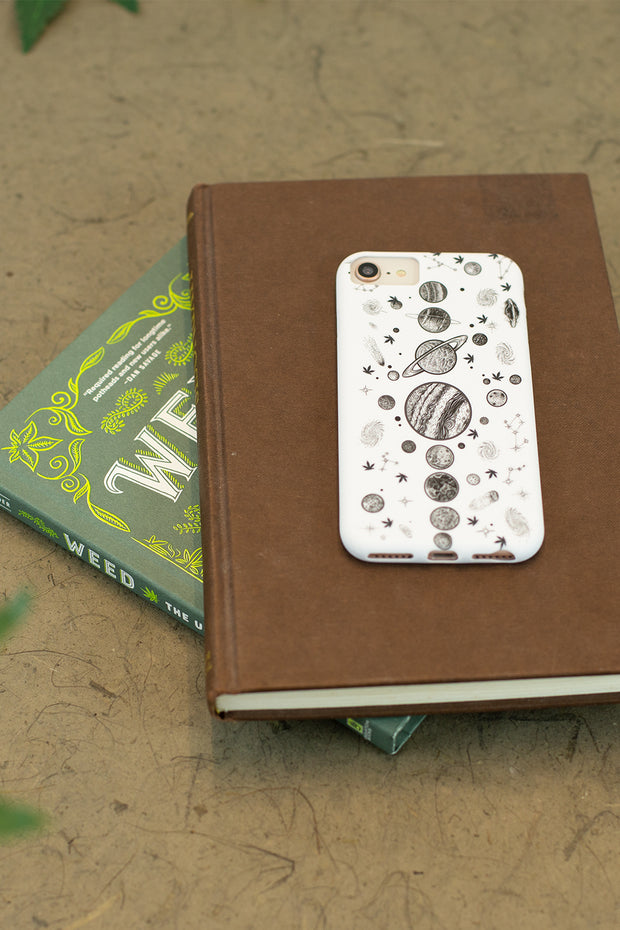 Lightly Toasted Planetary iPhone Case on pile of books