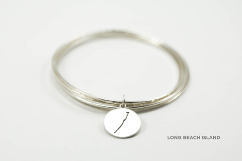 Stack of sterling silver hammered bangles featuring round Long Beach Island border with matte finish.