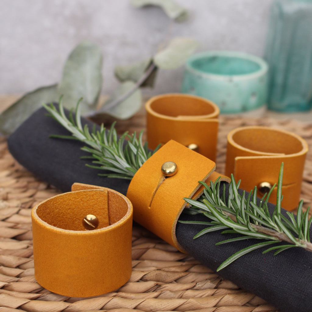 Set of mustard yellow leather napkin rings with brass stud fastening