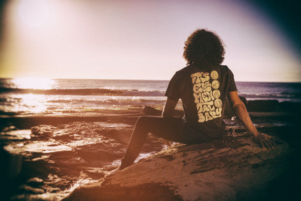 Model shot of a man wearing a t-shirt with Earthie's Elemental design, sitting on a rock looking out at the ocean.