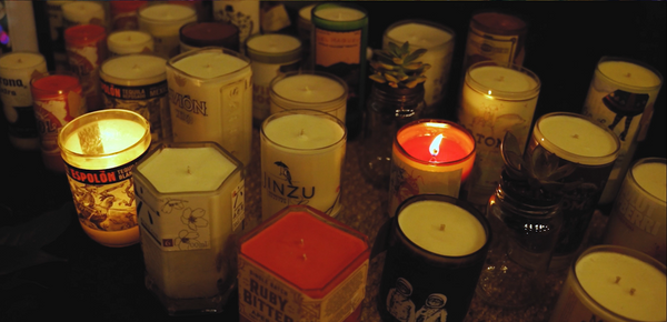 A selection of Earthie's candles made from up cycled wine and spirit bottles on display at a night market