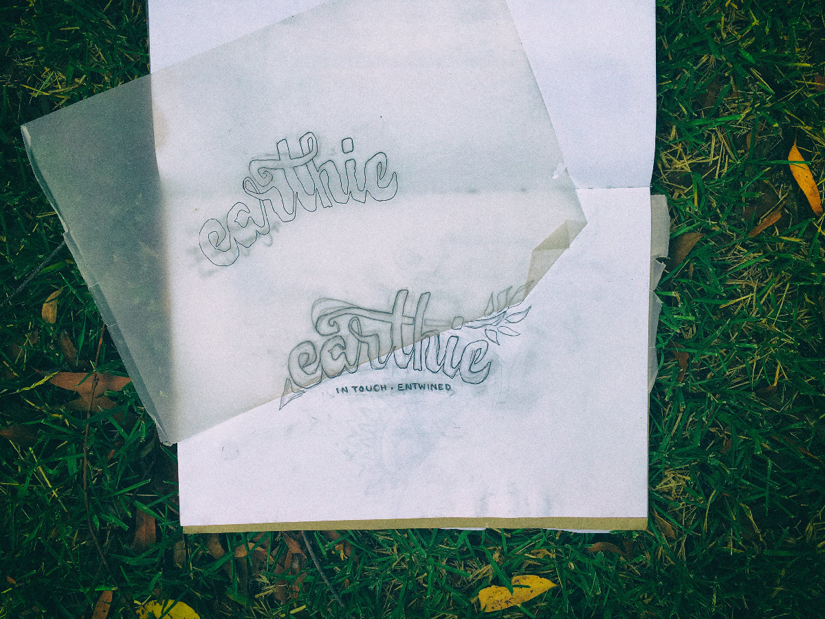 Concept art laid on a grass background – sketch drawings showing the initial stages of Earthie logo design.