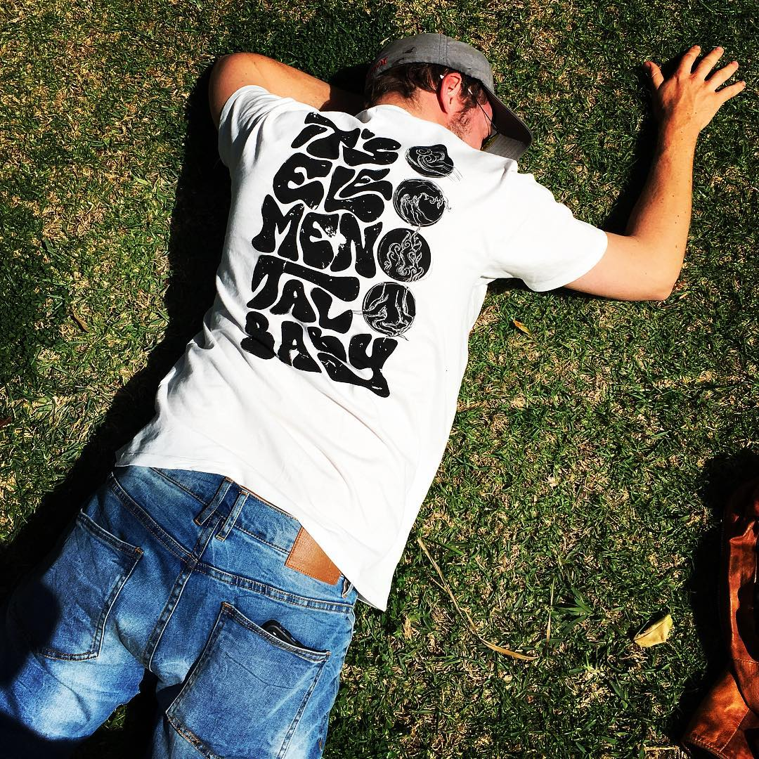 Male model face down lying on grass wearing Elemental Unisex Classic Tee in Stone Wash White with black lettering on back reading It`s Elemental Baby with 4 elements design alongside