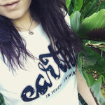 Model close up focusing on shirt standing next of lush green plants wearing Earthie Womens Rolled Sleeve Tee in  Stone Wash White with a Large Black Earthie Logo Front