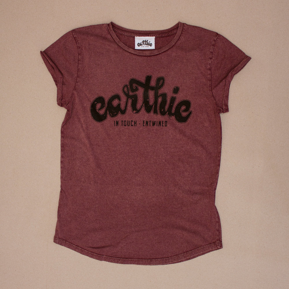 Front shot of Women Rolled Sleeve Tee  Stone Wash Burgundy  Large Earthie Logo across front of shirt
