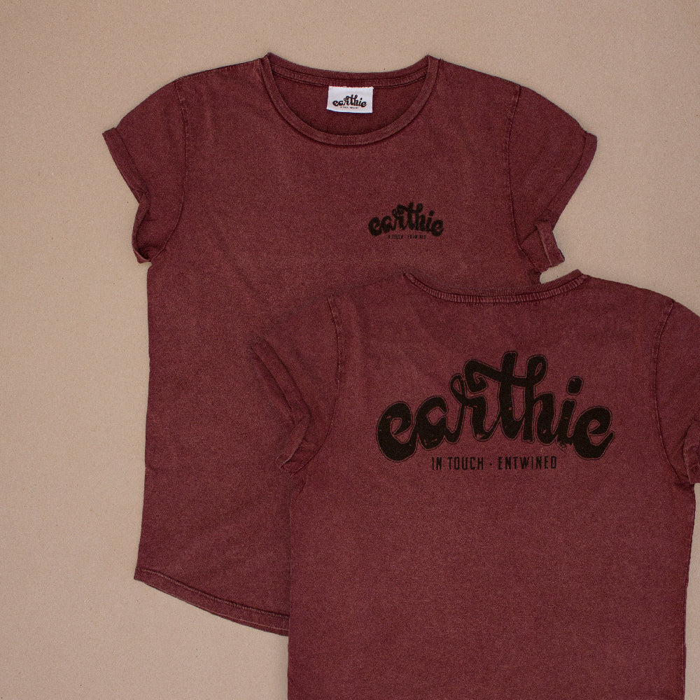 Two Womens Rolled Sleeve Tee in Stone Wash Burgundy grouped together, one showing the front of the garment with a small black Earthie logo printed on the front left chest position, the other showing the back of the shirt which has a large black Earthie logo printed across the shoulders.