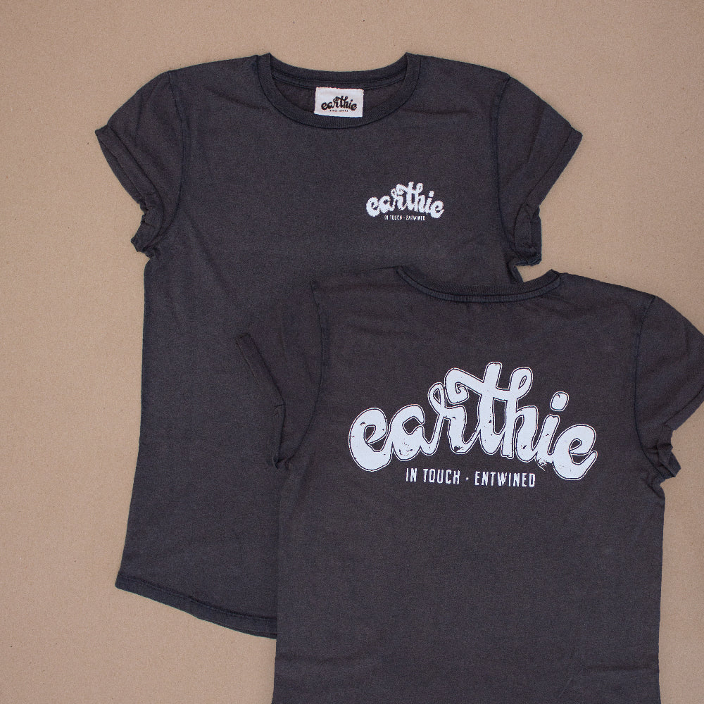 Two Womens Rolled Sleeve Tee in Stone Wash Denim grouped together, one showing the front of the garment with a small black Earthie logo printed on the front left chest position, the other showing the back of the shirt which has a large black Earthie logo printed across the shoulders.