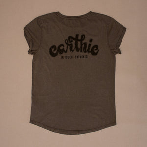 Front of a Womens Rolled Sleeve Tee in Stone Wash Grey, showing the back of the shirt which has a large black Earthie logo printed across the shoulders.