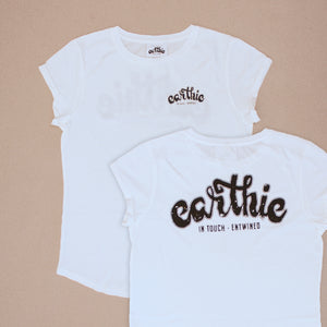 Two Womens Rolled Sleeve Tee in Stone Wash White grouped together, one showing the front of the garment with a small black Earthie logo printed on the front left chest position, the other showing the back of the shirt which has a large black Earthie logo printed across the shoulders.