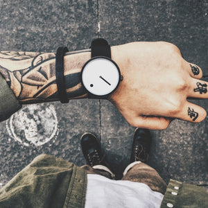cool man with tattoos wearing line and dot minimalist wrist watch