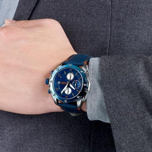 man in charcoal grey suit wearing water resistant blue face blue leather band chronograph analog quartz watch