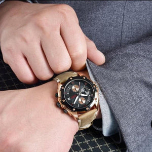 man in grey suit wearing water resistant black face brown leather band chronograph analog quartz watch