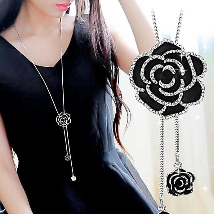 woman in black dress wearing black rose pendant