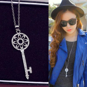 woman in hat and sunglasses wearing old fashioned key pendant