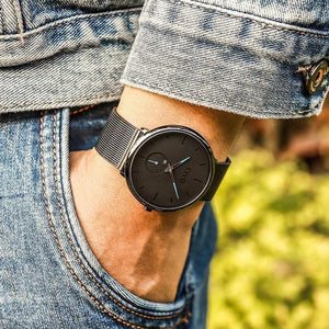 man with hand in jean pocket wearing ultra thin modern black azure dial watch for men