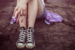 Picture of a girls legs and feet in sneakers