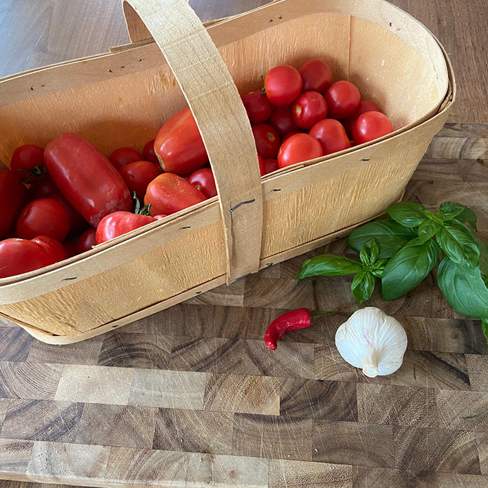 Basket of tomatoes, garlic, basil and hot peppers
