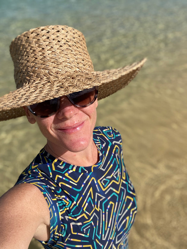 Ash Co Founder in Moreton Island wearing one piece swimsuit and Lack of Color hat