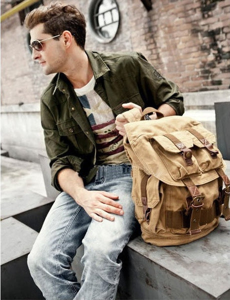 Man holding light brown military travel backpack