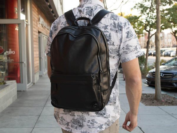 Man wearing the unisex black leather backpack by Serbags