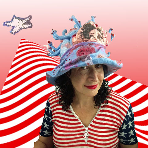 Pink and Blue Covid-19 inspired hat against a red and white striped background.