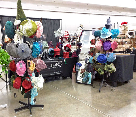 Photo of my felted hats arranged on hat rack and table at last year's Handmade Arcade.