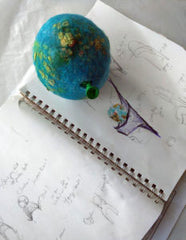 Sketchbook of hat shapes with felted globe