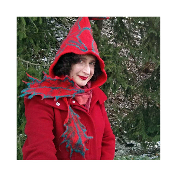 Red Felted Hood with holly ties in front of pine trees.