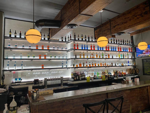 bar shelves illuminated with bright white light and colorful bottle display
