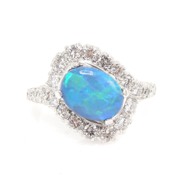 Oval Black Opal Surrounded by a Swirl of Diamonds in White Gold