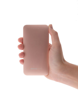 Hånd som holder rosa powerbank 5000mah som lader mobilen din