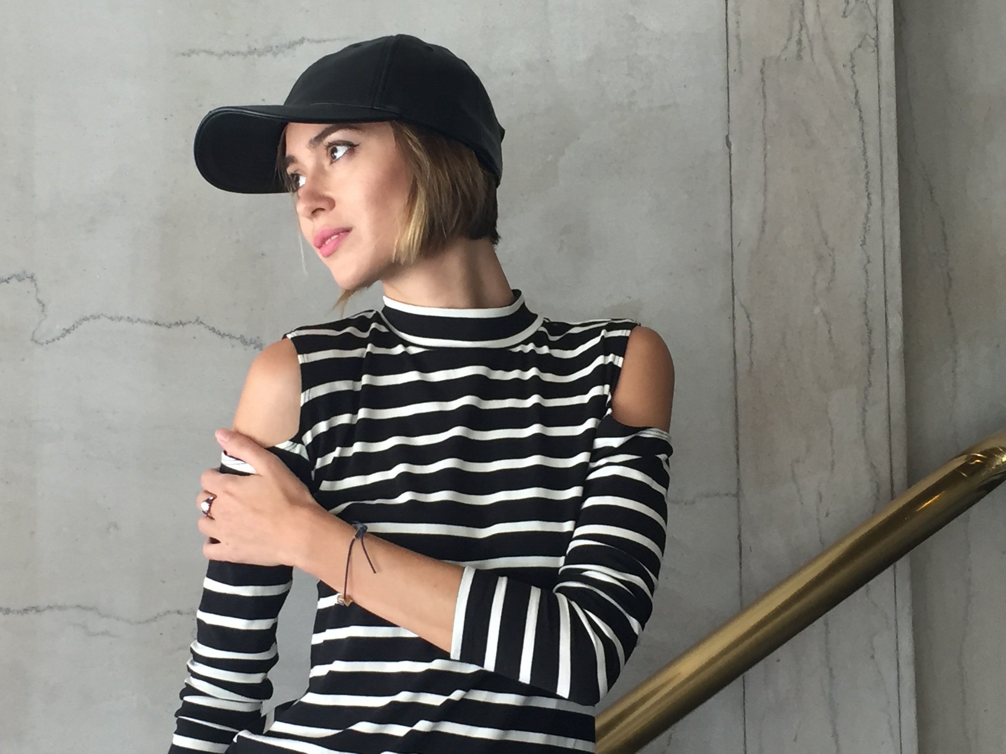 Long sleeve cold shoulder mock neck top in black and white stripes.
