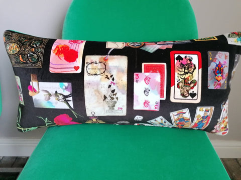 A bolster cushion made from Christian Lacroix Maison des Jeux fabric.