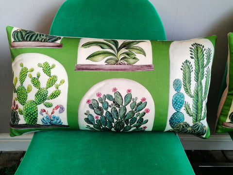 Long bolster cushion which features cacti, succulents and a beautiful orchid