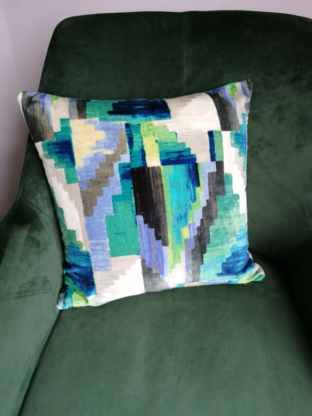 One of a pair of cushions made from an abstract kaleidoscopic velvet in beautiful shades of blue and green.