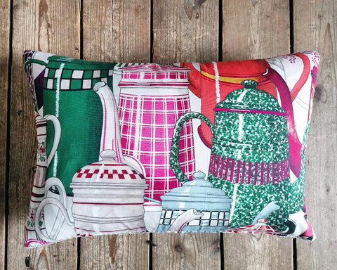 Bolster cushion made from fabric by Manuel Canovas featuring pink French enamel coffee pots!
