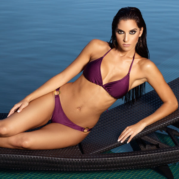 Ring Mauve Bikini by Tequila Beach Swimwear, model sits on pool chair, purple triangle bikini with golden ring at hips