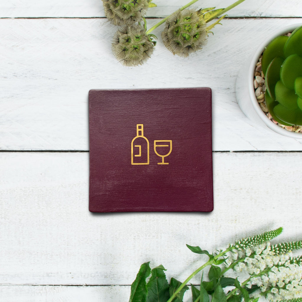 Burgundy square coaster with wine graphic symbol