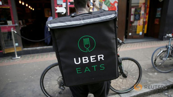 Uber eats cyclist courier delivering food by bike