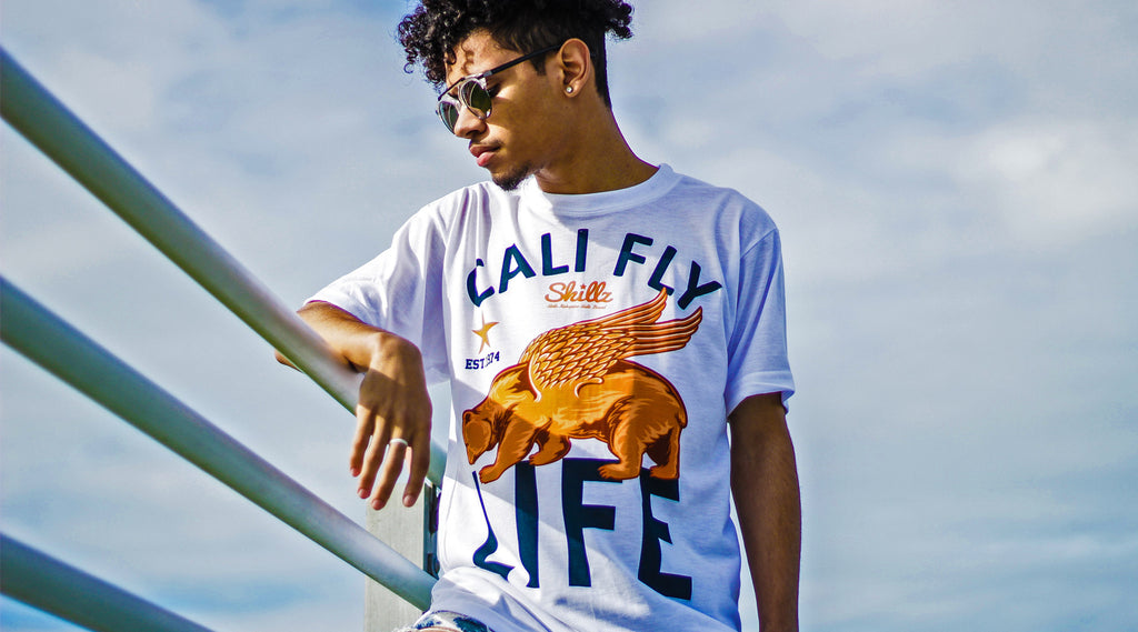 Cali Fly Life. Young man with sky behind him wearing a t-shirt.