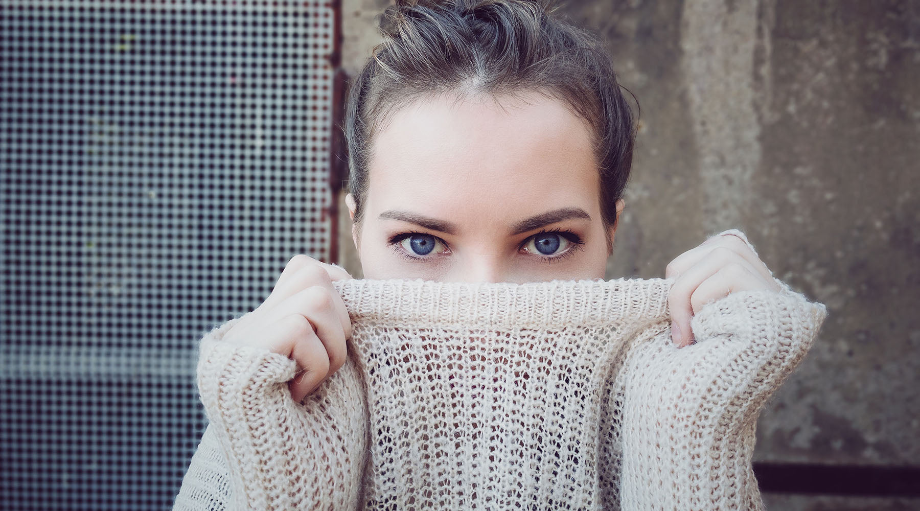 woman covering her nose with her sweater
