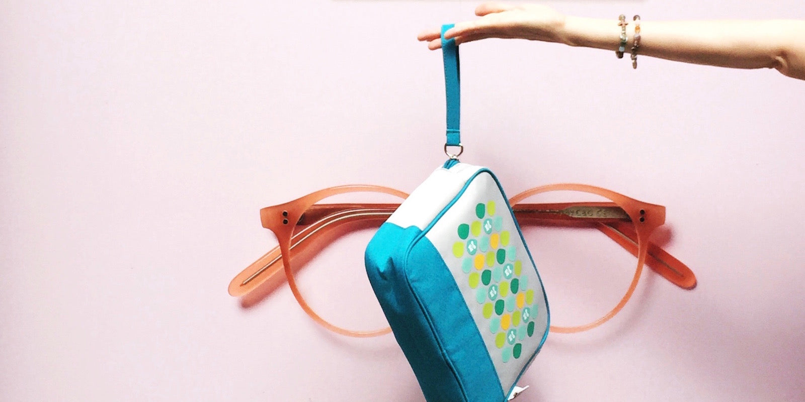 Beyond the bag with our Popdots Go Pouch toiletry travel bag with a poster of large glasses behind our bag