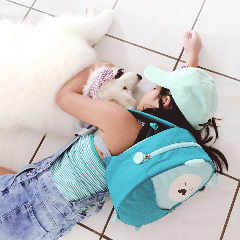 Little girl hugging a white puppy and wearing a Milkdot blue mini backpack