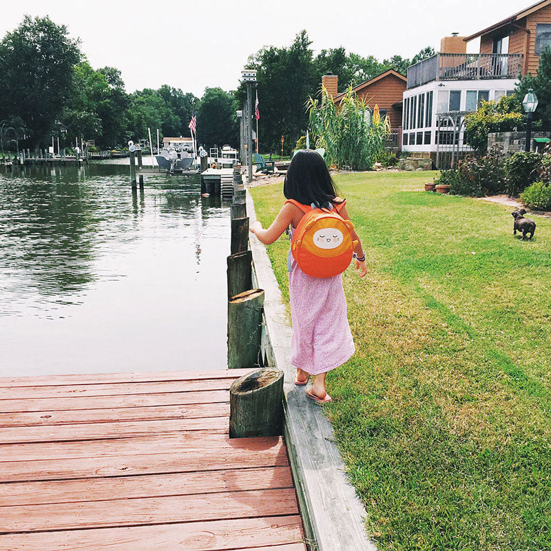 Girl walking by a waterfront, wearing a Charlie Kawaii Pac toddler backpack by Milkdot.
