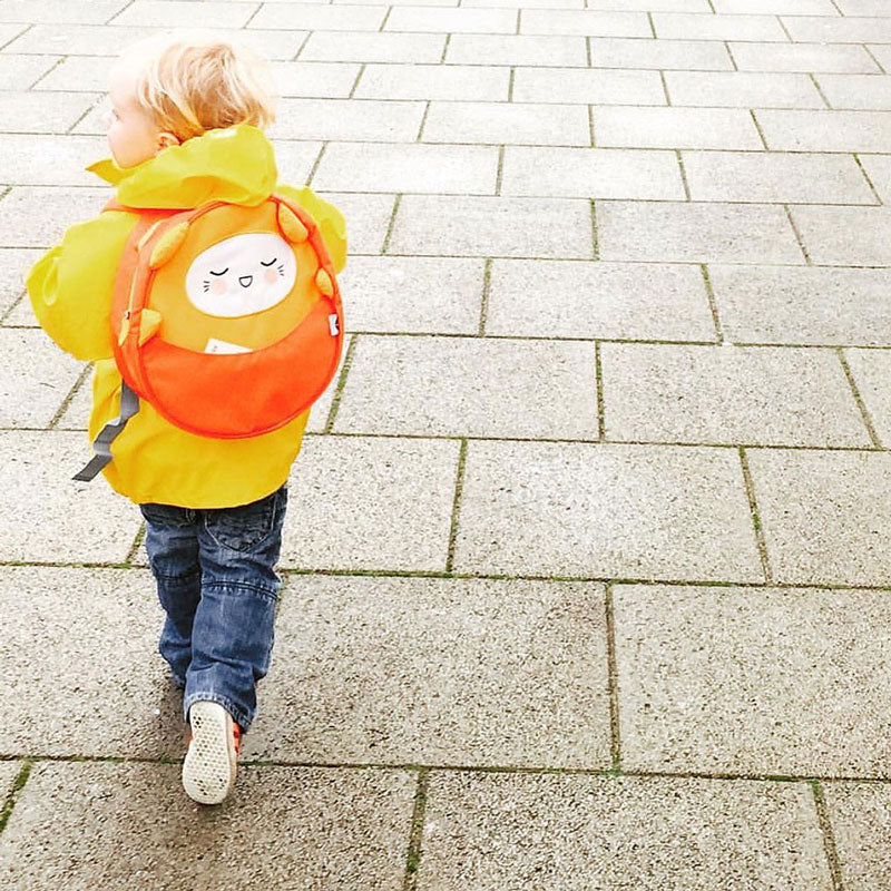 Toddler wearing a yellow raincoat and a Milkdot orange toddler backapack.