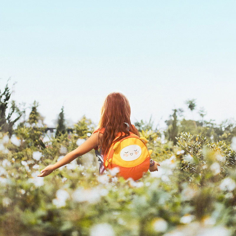 Girl with red hair in flower field wearing an orange Milkdot toddler backpack.