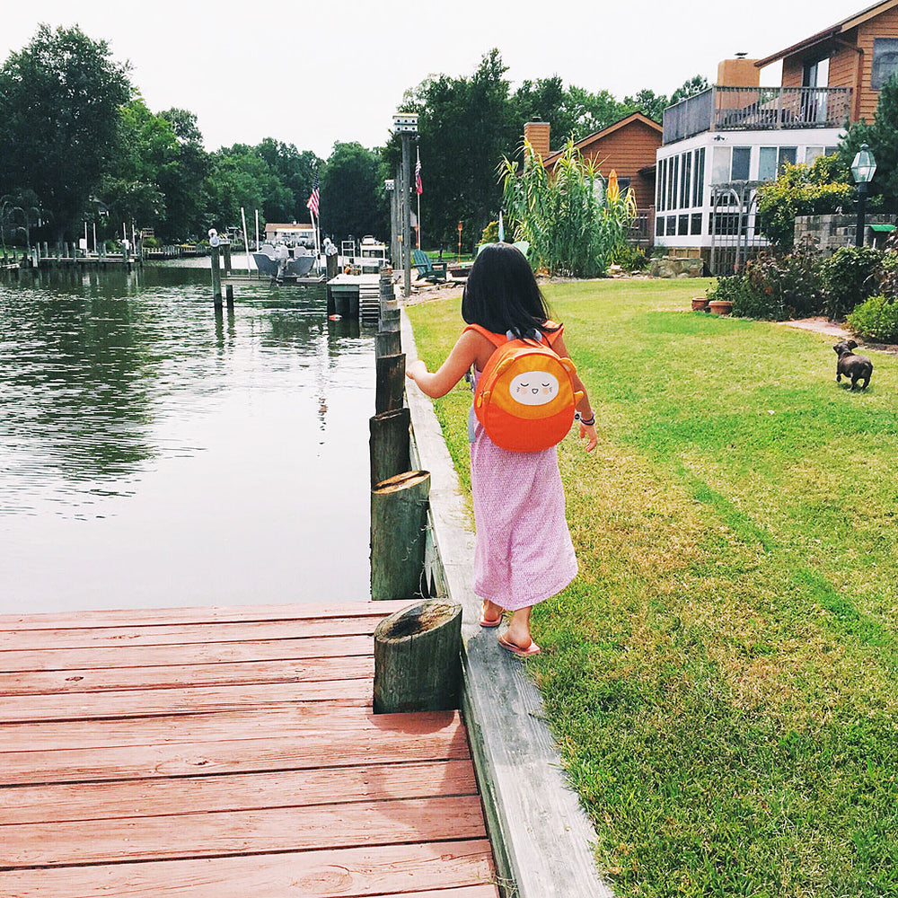 little girl walking by the water and wearing our Charlie mini backpack