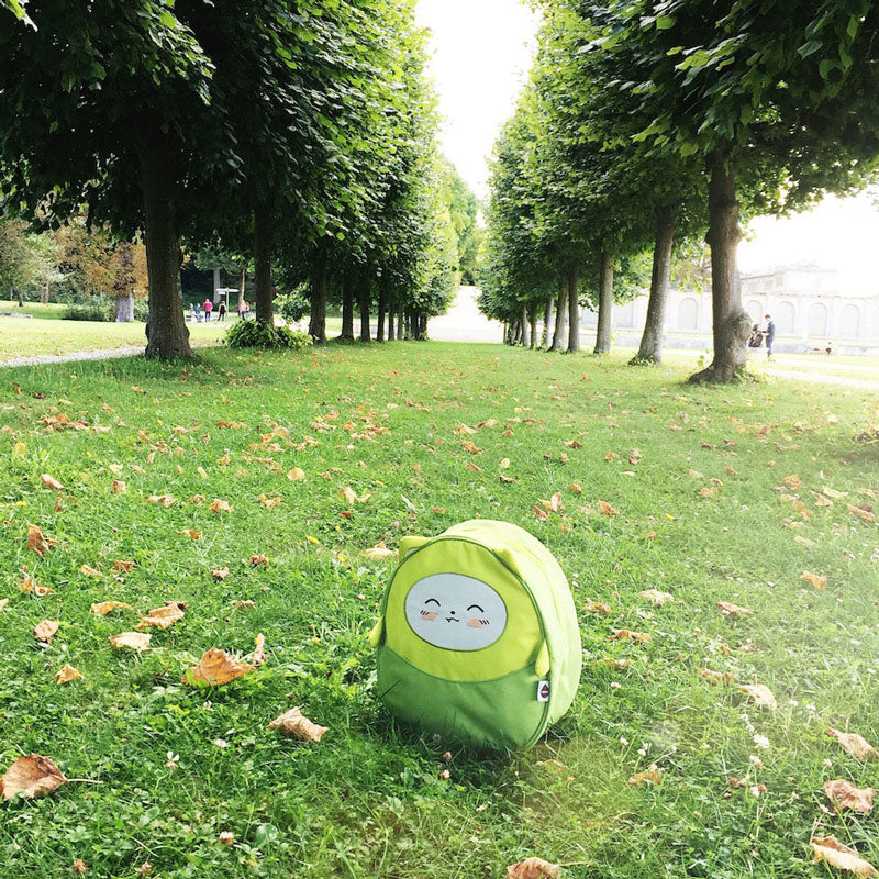 Green Milkdot toddler backpack on a green lawn with trees.