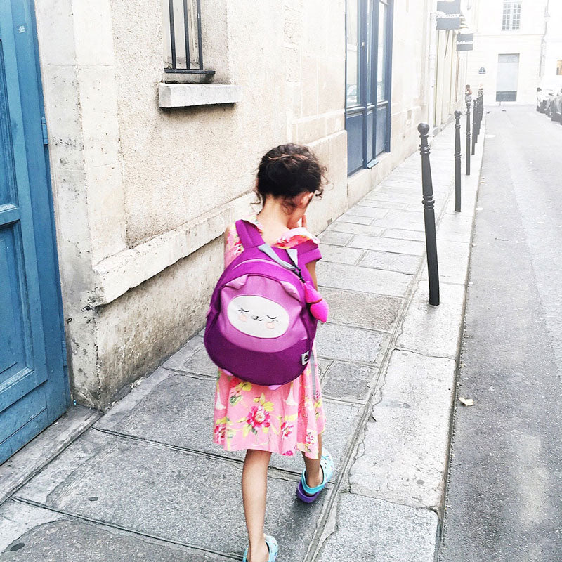 Little girl walking on a Parisian street wearing a Milkdot purple preschool backpack.